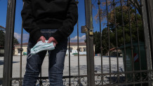 μαθητής με μάσκα στα χέρια έξω από σχολείο