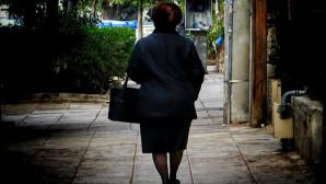 Ηλικιωμένη γυναίκα περπατά στο πεζοδρόμιο