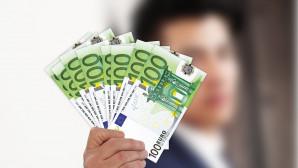 Άνδρας κρατά χαρτονομίσματα των 50 ευρώ