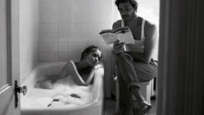 Ένας άνδρας διαβάζει στη σύντροφό του την ώρα που εκείνη κάνει μπάνιο