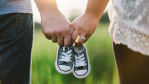Ερωτευμένο ζευγάρι κρατά παπουτσάκια μωρου
