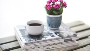 φλιτζάνι καφέ πάνω σε περιοδικά