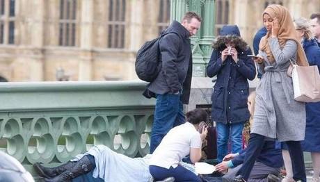 Γυναίκα με μαντήλα που αδιαφορεί για τραυματία στο Λονδίν