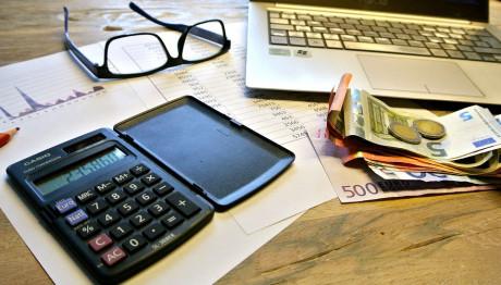 Χρήματα, γυαλιά και κομπιούτερ σε τραπέζι για τον υπολογισμό φόρου