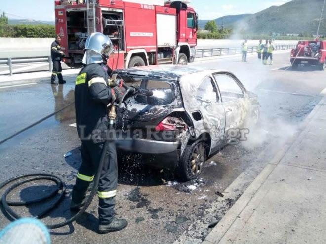 Πυροσβέστες που έφτασαν στο σημείο σβήνουν τις φλόγες από το αυτοκίνητο