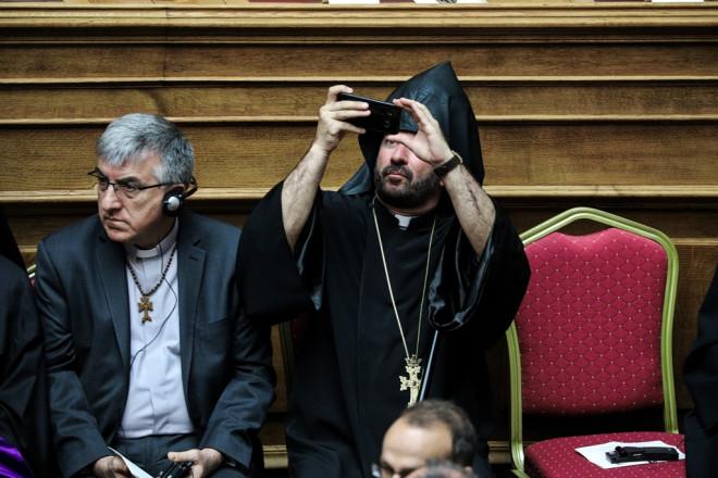 Ιερέας τραβά φωτογραφίες στην αίθουσα της Ολομέλειας