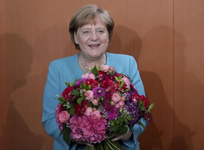 Η Μέρκελ με τα λουλούδια που της χάρισαν οι συνεργάτες της για τα γενέθλιά της