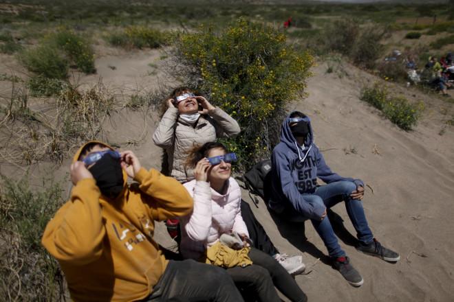 Κόσμος παρατηρεί το φαινόμενο με ειδικά γυαλιά στην Αργεντινή- AP Photo/Natacha Pisarenko