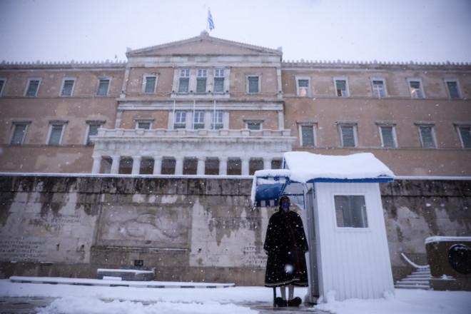 Εύζωνας στο μνημείο του Άγνωστου Στρατιώτη με φόντο το χιονισμένο κτίριο της Βουλής - φωτογραφία Eurokinissi