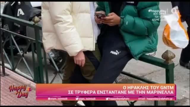 βλέπουμε τον Ηρακλή να κάθεται και να κοιτάζει κάτι στο κινητό του και τη Μαρινέλα σχεδόν να έχει μπει στην αγκαλιά του