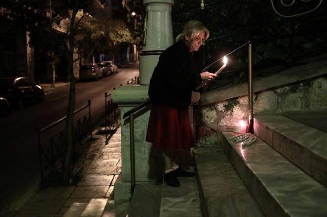γυναίκα παίρνει το Άγιο Φως από εκκλησία