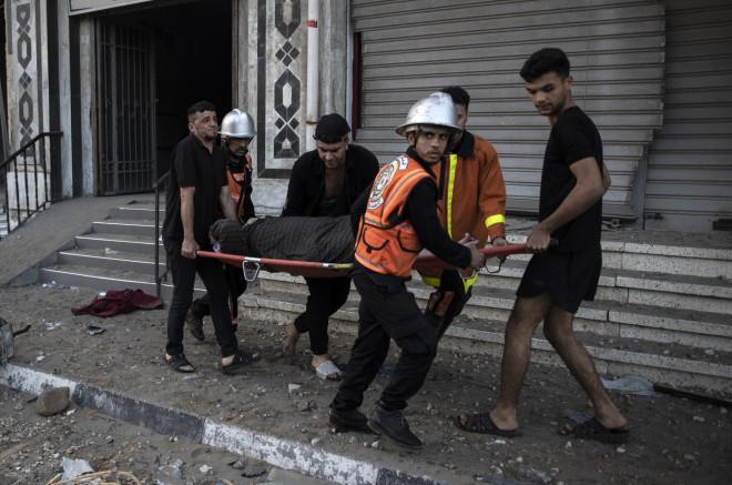 Παλαιστίνιοι διασώστες μεταφέρουν ηλικιωμένη μετά από χτύπημα ρουκέτας στο διαμέρισμά της-φωτογραφία ΑΡ
