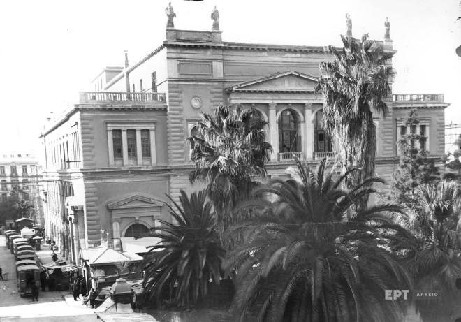 Γενική άποψη του Δημοτικού Θεάτρου από την πλευρά της οδού Αιόλου το οποίο βρισκόταν στην Πλατεία Δημαρχείου (μετέπειτα Πλατεία Κοτζιά και σημερινή Πλατεία Εθνικής Αντίστασης). Γκρεμίστηκε επι θητείας του υπουργού Διοικήσεως Πρωτευούσης Κωνσταντίνου Κοτζιά. Δεκαετία 1920. Φωτογραφία: Π.Πουλίδης / Αρχείο ΕΡΤ