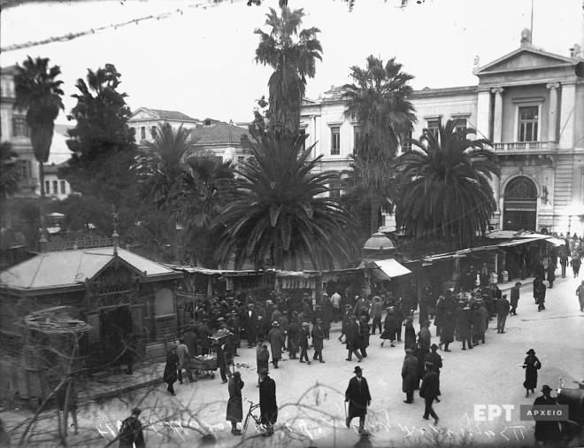 Άποψη της Πλατείας Δημαρχείου, σημερινή Πλατεία Εθνικής Αντίστασης, με υπαίθρια μαγαζιά. Στο βάθος το Μέγαρο της Εθνικής Τράπεζας επί της οδού Αιόλου. Δεκαετία 1920. Φωτογραφία: Π.Πουλίδης / Αρχείο ΕΡΤ