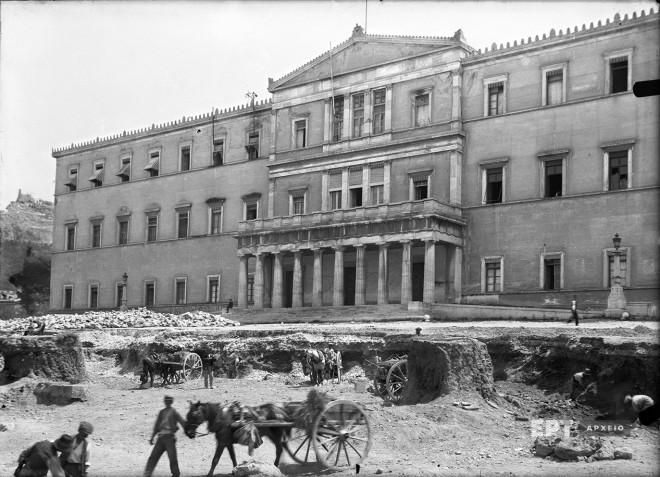Παλαιά ανάκτορα, σημερινή Βουλή. Γενική άποψη του κτιρίου από τη Λεωφόρο Αμαλίας κατά τη διάρκεια των εργασιών εκχωμάτωσης του χώρου για την κατασκευή της πλατείας του Μνημείου του Άγνωστου Στρατιώτη, 1929. Φωτογραφία: Π.Πουλίδης / Αρχείο ΕΡΤ