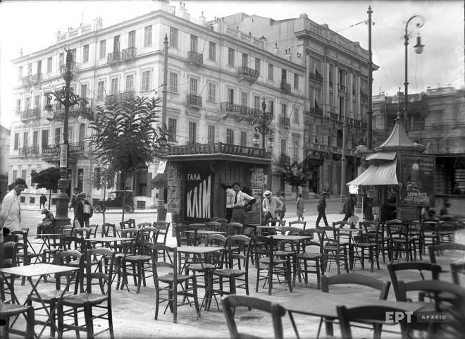 Άποψη της Πλατείας Συντάγματος προς την πλευρά της οδού Ερμού και του ξενοδοχείου Grand Hotel d' Angleterre. Σε πρώτο πλάνο τα τραπεζάκια του καφέ-ζαχαροπλαστείου του Ζαβορίτη που στεγαζόταν στο ισόγειο του Μεγάρου Κορομηλά. Δεκαετία 1920. Φωτογραφία: Π.Πουλίδης / Αρχείο ΕΡΤ