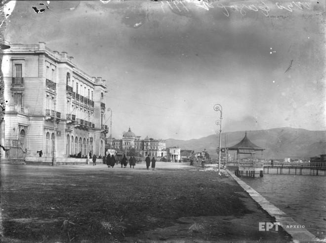 Νέο Φάληρο. Άποψη της παραλίας κατά τη δεκαετία του 1920. Στα αριστερά το Μέγα ξενοδοχείον. Στα δεξιά το κιόσκι, όπου πραγματοποιούνταν μουσικές εκδηλώσεις, και η εξέδρα της περιοχής που προσχωρούσε μέσα στη θάλασσα, τόπος συνάντησης και περιπάτου. Στο βάθος το ξενοδοχείο ''Ακταίον''. Φωτογραφία: Π.Πουλίδης / Αρχείο ΕΡΤ