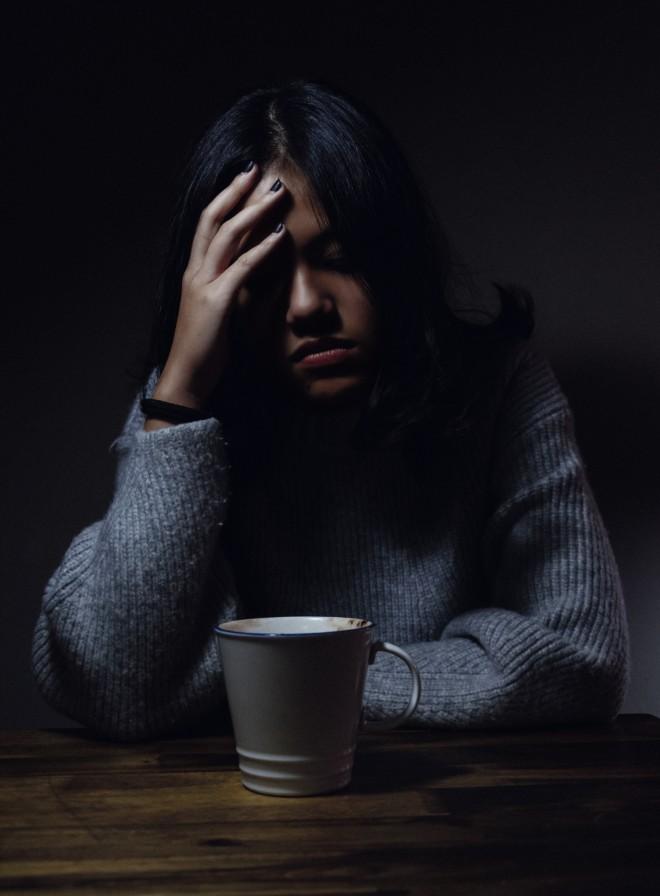 Προβληματισμένη έφηβη κάθεται στο τραπέζι πιάνοντας το κεφάλι της