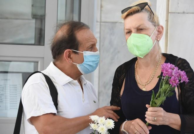 Ο Σπύρος Μπιμπίλας και η Ρουμπίνη Βασιλακοπούλου με μωβ λουλούδια στο χέρι / φωτογραφία NDP