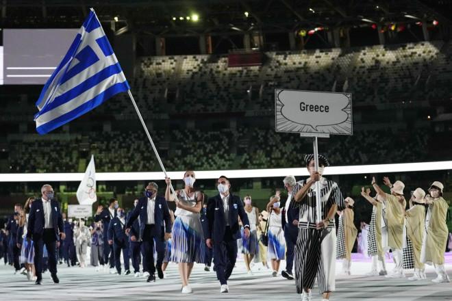 ΗΆννα Κορακάκη κρατά την ελληνική σημαία με τονΛευτέρη Πετρούνιαδίπλα της- φωτογραφία ΑΡ