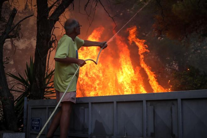 Κάτοικος προσπαθεί να περιορίσει τη φωτιά ρίχνοντας νερό με λάστιχο-φωτογραφία Eurokinissi
