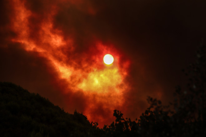 Oι φλόγες και ο καπνός κάλυψαν τον ήλιο-φωτογραφία Eurokinissi