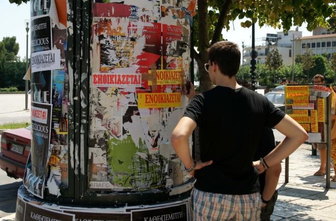 Νεαρός φοιτητής, διαβάζει αφίσες με ενοικιάζεται κολλήμενες σε κολώνα