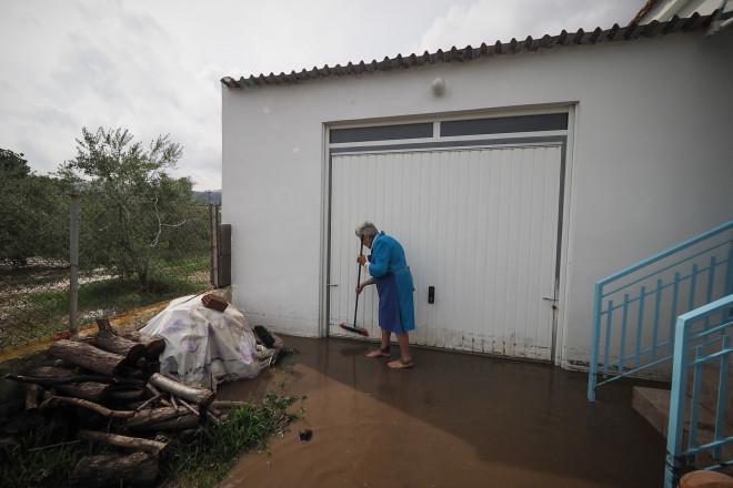 Γυναίκα προσπαθεί να απομακρύνει τα νερά από το σπίτι της στη Βόρεια Εύβοια/EUROKINISSI