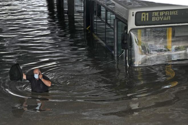 Ο οδηγός απομακρύνεται από το λεωφορείο που«κόλλησε» στα νερά- Και ο ίδιος είναι καλυμμένος μέχρι τη μέση/ φωτογραφία ΑΡ