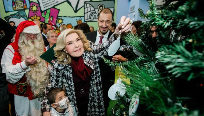 Η Μαριάννα Β. Βαρδινογιάννη μαζί με ένα παιδί τοποθετεί το πρώτο στολίδι