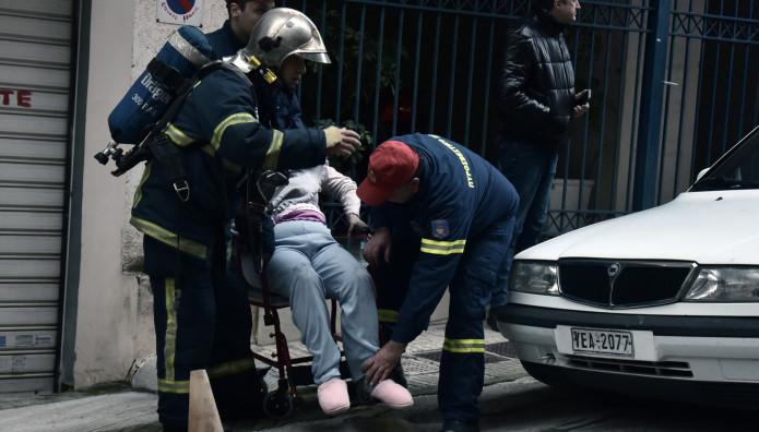 Οι πυροσβέστες βοηθούν τη μια γυναίκα να βγεί από το διαμέρισμα/ Intimenews