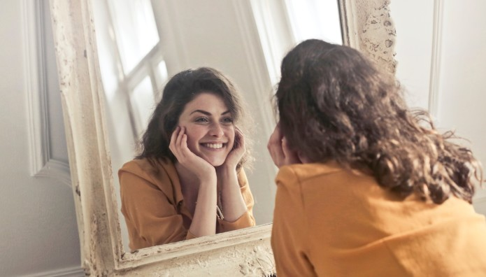Γυναίκα που χαμογελάει στον καθρέφτη