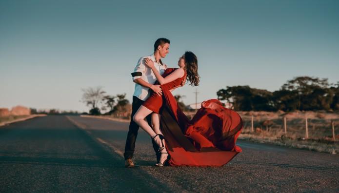 ζευγάρι χορεύει στον δρόμο, κοπέλα με κόκκινο φόρεμα